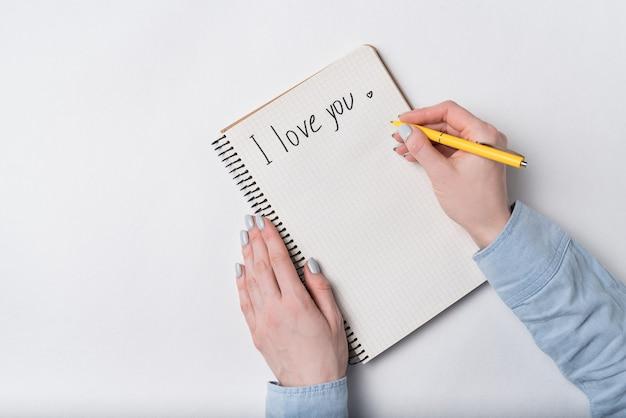 Vrouwelijke hand die in notitieboekje de woorden schrijft i love you. bovenaanzicht van notebook en handen. witte achtergrond