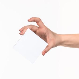 Vrouwelijke hand die leeg document voor verslagen op wit houdt.