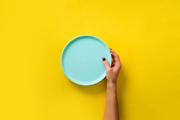 Vrouwelijke hand die lege blauwe plaat op gele achtergrond met exemplaarruimte houdt.