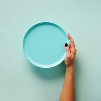 Vrouwelijke hand die lege blauwe plaat op pastelkleurachtergrond houdt met exemplaarruimte
