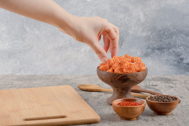 Vrouwelijke hand die macaroni uit houten kom op marmeren achtergrond neemt