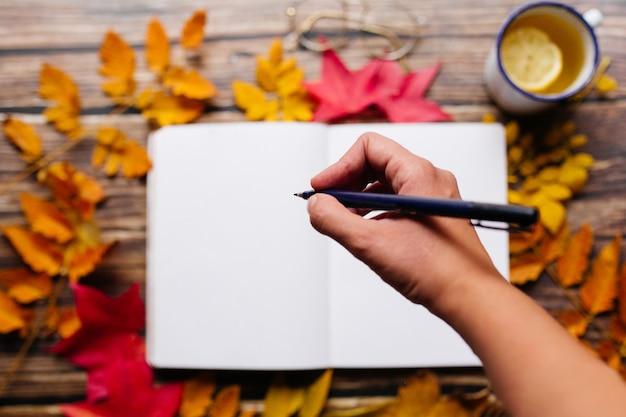 Vrouwelijke hand die met een pen in een kogeldagboek schrijft. lege kladblok-pagina in een gezellige ruimte met emaille kopje citroen gemberthee, glazen en kleurrijke bladeren op een houten tafel.