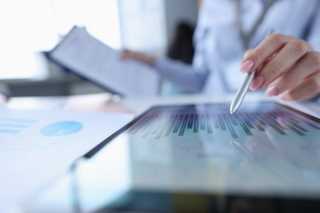 Vrouwelijke hand die met stylus richt om op tabletclose-up in kaart te brengen