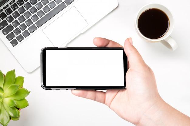 Vrouwelijke hand die mobiele slimme telefoon met het lege witte scherm houdt tegen moderne laptop, koffie en groene installatie.