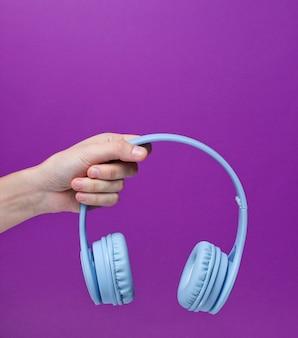 Vrouwelijke hand die moderne draadloze blauwe hoofdtelefoons op een purpere achtergrond houdt.