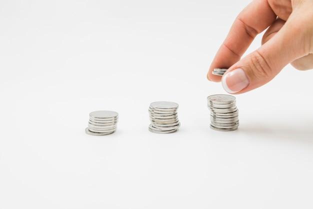 Vrouwelijke hand die muntstukken op stapel zet