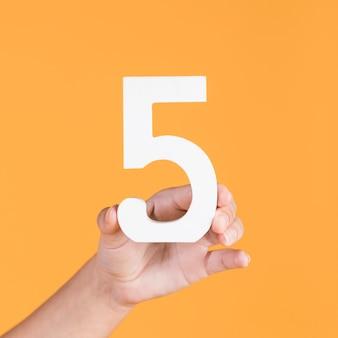 Vrouwelijke hand die nummer 5 steunt tegen een gele achtergrond