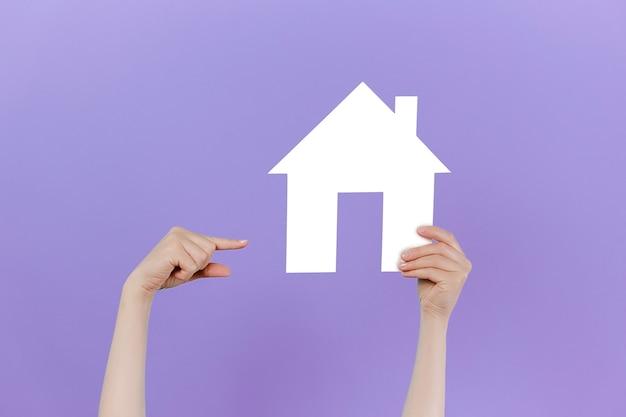 Vrouwelijke hand die opheft en naar een klein huis wijst