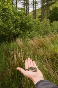 Vrouwelijke hand die ouderwets kompas houdt dat de manier toont