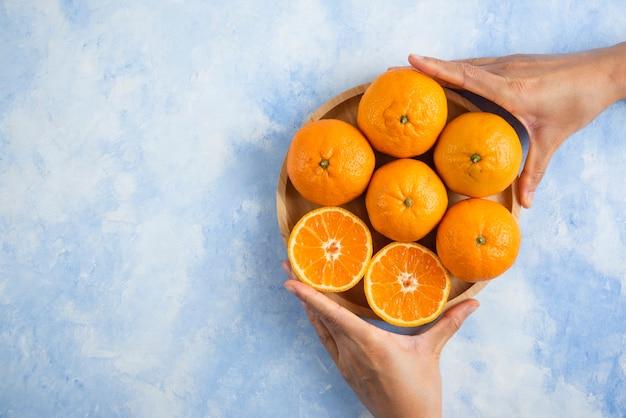 Vrouwelijke hand die plak van stapel neemt. clementine mandarijnen op blauwe ondergrond