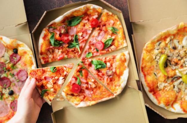 Vrouwelijke hand die plak van verse pizza van leveringsdoos neemt. bovenaanzicht, donkere achtergrond. junk food