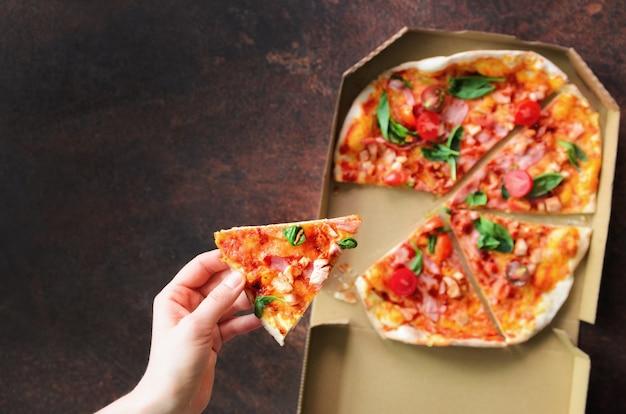 Vrouwelijke hand die plak van verse pizza van leveringsdoos neemt.