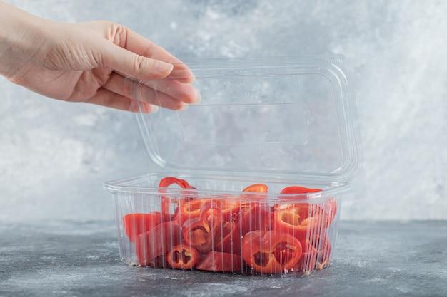 Vrouwelijke hand die plastic container opent, plastic container vol met gesneden rode paprika's