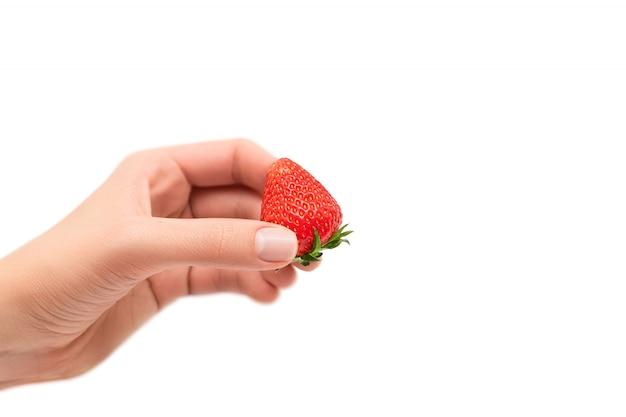 Vrouwelijke hand die rijpe rode aardbei houdt die op witte achtergrond wordt geïsoleerd.