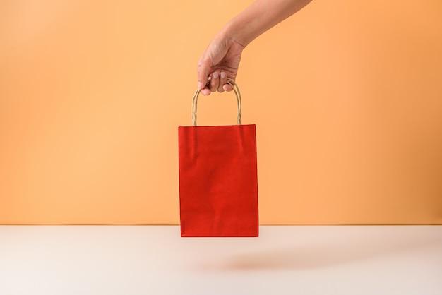 Vrouwelijke hand die rode papaer het winkelen zakken houdt