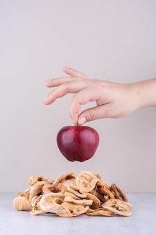 Vrouwelijke hand die rode rijpe appel over steen houdt