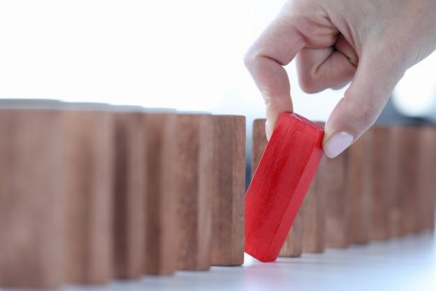 Vrouwelijke hand die rood houten blok uit lijnclose-up het implementatieconcept van het bedrijfsidee terugtrekt