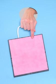 Vrouwelijke hand die roze document zak op blauw houdt