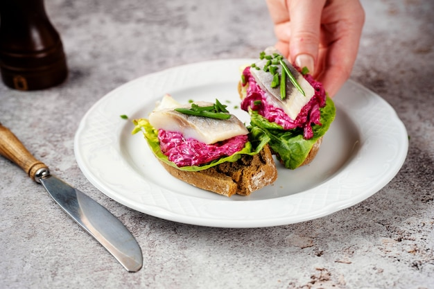 Vrouwelijke hand die sandwich met haring, bieten en groene salade van plaat neemt
