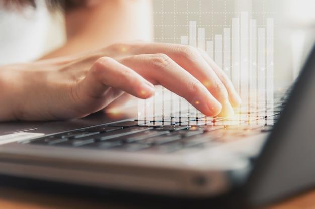 Vrouwelijke hand die toetsenbord met financiële grafiek gebruikt
