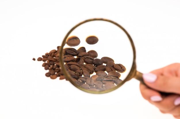Vrouwelijke hand die vergrootglas over de koffiebonen houdt