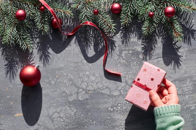Vrouwelijke hand die verpakte kerstmisgift met rode snuisterij houdt. kerst plat lag op abstracte acryl vloeibare vloeistof schilderij. grensslinger van natuurlijke dennentakjes en rode ballen met lange schaduwen.