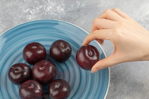 Vrouwelijke hand die verse pruimen neemt van blauw bord.