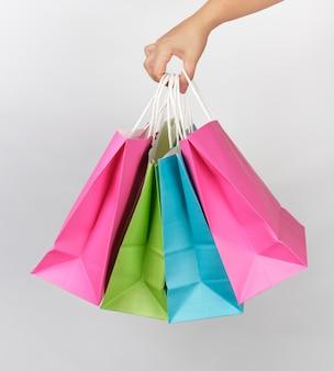 Vrouwelijke hand die vier gekleurde document het winkelen verpakkende zakken houdt