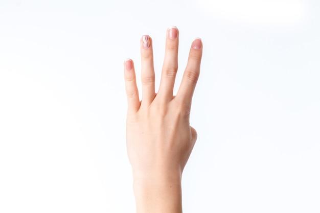 Vrouwelijke hand die vier vingers close-up toont die op witte achtergrond wordt geïsoleerd