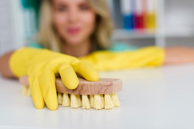 Vrouwelijke hand die wit bureau met houten borstel schoonmaakt