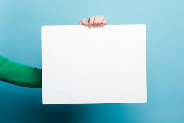 Vrouwelijke hand die wit leeg malplaatjedocument over blauwe muur houdt