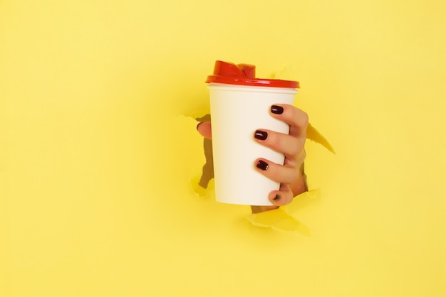 Vrouwelijke hand die witboekmok op gele achtergrond houdt.
