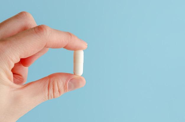 Vrouwelijke hand die witte capsule op blauwe achtergrond houdt