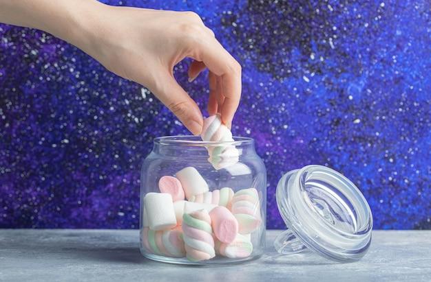 Vrouwelijke hand die zachte kleurrijke marshmallows uit glazen pot haalt