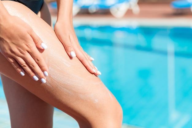 Vrouwelijke hand die zonnebrandcrème op haar been aanbrengt bij het zwembad. zonbeschermingsfactor in vakantie, concept.