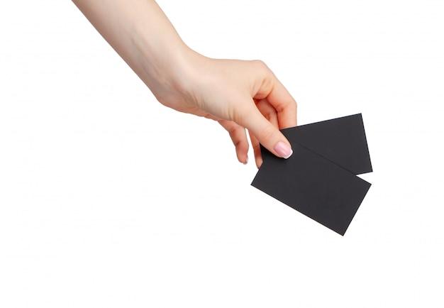 Vrouwelijke hand die zwarte businesscard houdt die op witte achtergrond wordt geïsoleerd