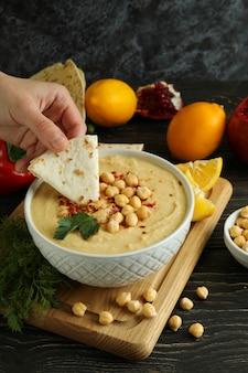 Vrouwelijke hand dips pita in smakelijke hummus op houten tafel