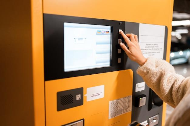 Vrouwelijke hand drukt op de knop op een betaalterminal parkeren.