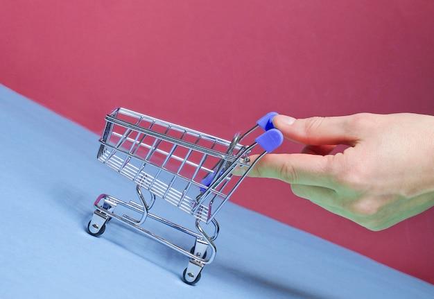 Vrouwelijke hand duwt schuin leeg mini winkelwagentje omhoog. winkelen concept, levering