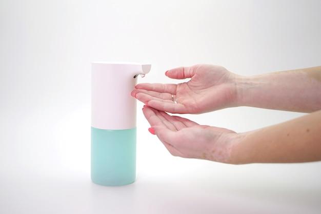 Vrouwelijke hand en automatische automaat, ontsmettingsmiddel op een geïsoleerde muur, close-up. demonstratie van handhygiëne, preventie van de verspreiding van coronavirus