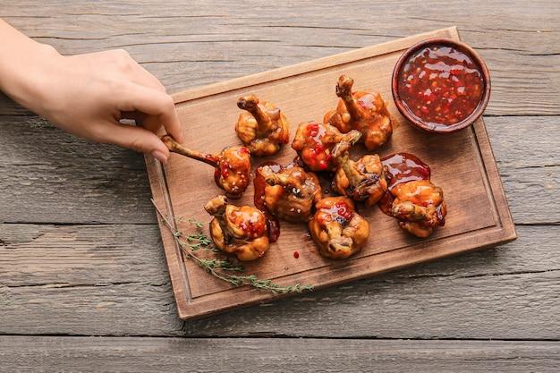 Vrouwelijke hand en bord met lekkere kip lollies op houten oppervlak