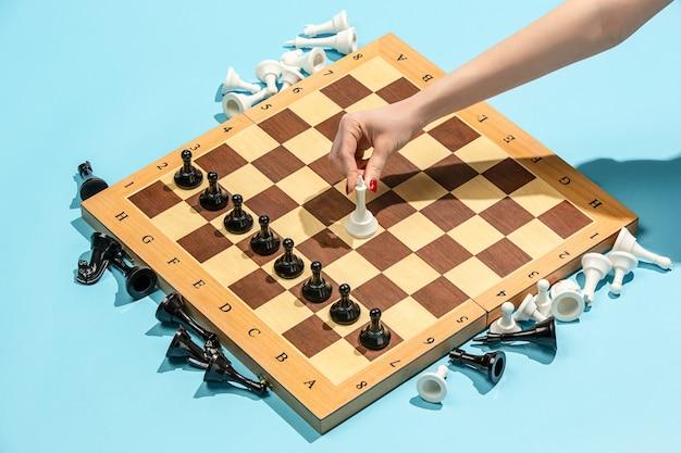 Vrouwelijke hand en schaakbord, spelconcept.