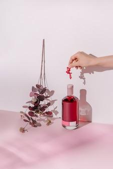 Vrouwelijke hand, fles alcoholische drank met rood fruit op pastelroze en paarse achtergrond.