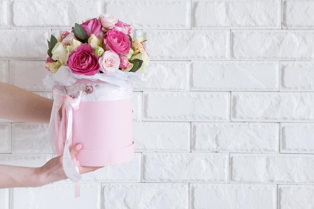 Vrouwelijke hand geeft bos met roze en gele rozen op witte bakstenen achtergrond. cadeau voor moeder of vrouw, bloemistenwerk, bruiloftsdecor, mooi boeketverkoopconcept