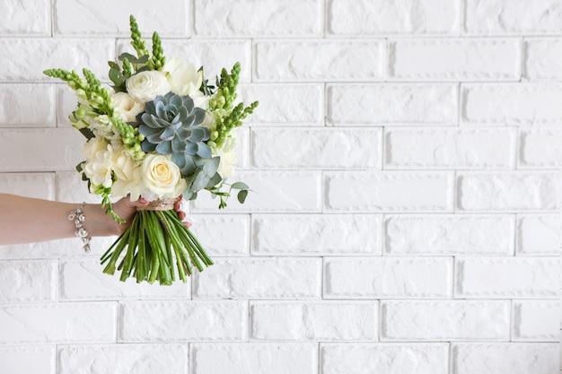 Vrouwelijke hand geeft bos met rozen en sappig op witte bakstenen achtergrond. cadeau voor moeder of vrouw, bloemistenwerk, bruiloftsdecor, mooi boeketverkoopconcept