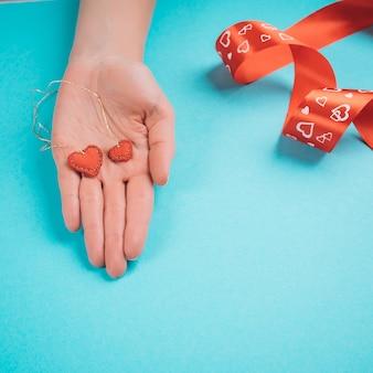 Vrouwelijke hand geeft handgemaakte harten.
