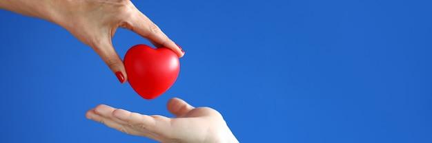 Vrouwelijke hand geeft rood hart door aan mannenhand. vriendelijkheid en liefdadigheid concept