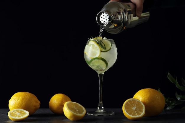 Vrouwelijke hand giet cocktail in glas op donker