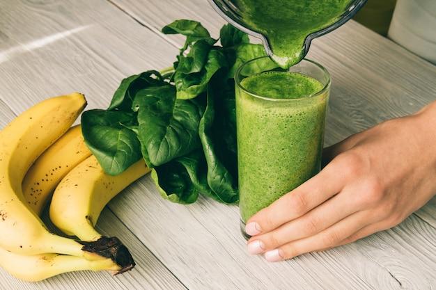Vrouwelijke hand giet een smoothie van banaan en spinazie in glas op een houten achtergrond