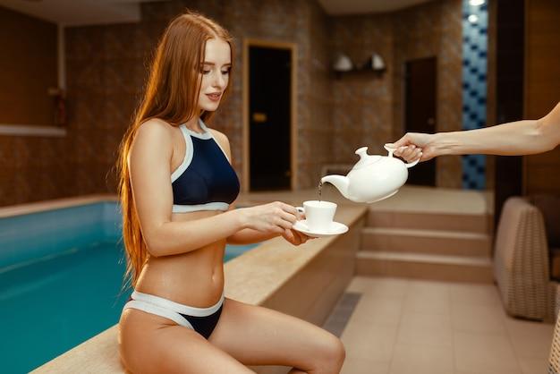 Vrouwelijke hand giet thee voor vrouw in zwembroek bij het zwembad binnenshuis.